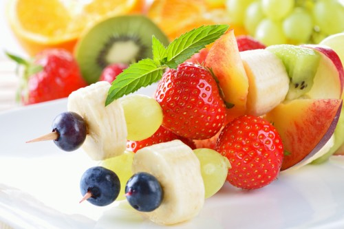 Une belle brochette de fruits avec des bananes, kiwis, et raisins